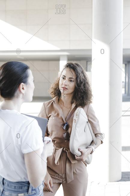 Beautiful businesswomen talking outside office building