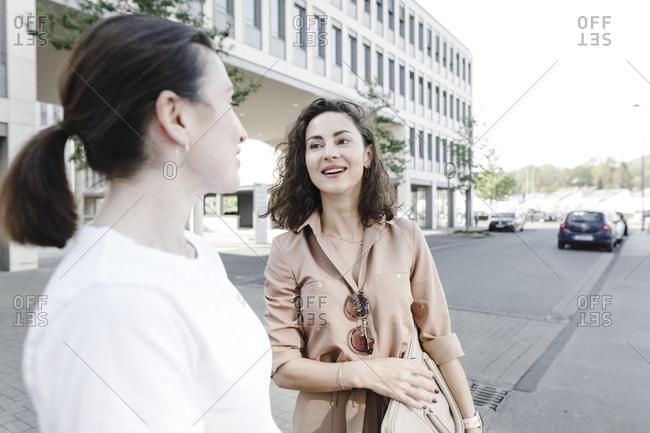 Happy businesswomen talking on street outside office building