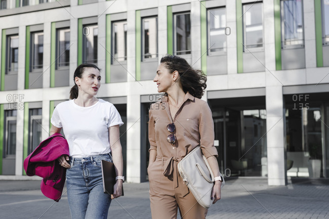 Multi-ethnic businesswomen talking while walking against office building