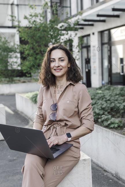 Portrait of confident businesswoman using laptop outside office building