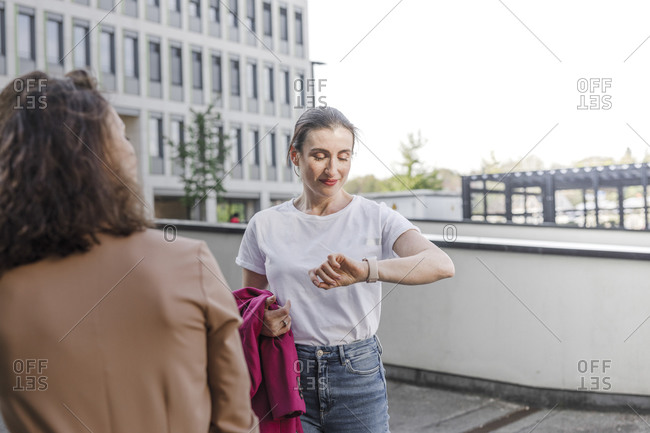 Businesswoman checking smart watch while standing with colleague outside office building
