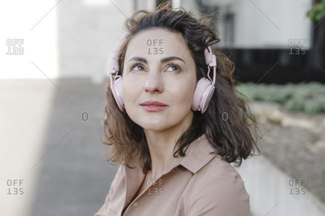 Thoughtful businesswoman listening music through headphones during sunny day
