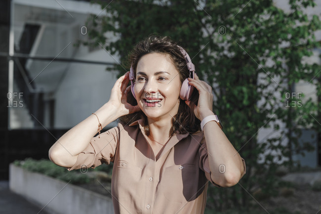 Happy businesswoman wearing headphones during sunny day