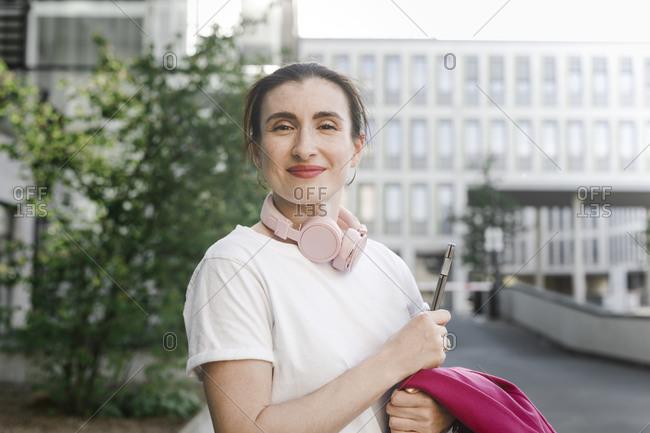Portrait of confident businesswoman holding laptop against office building