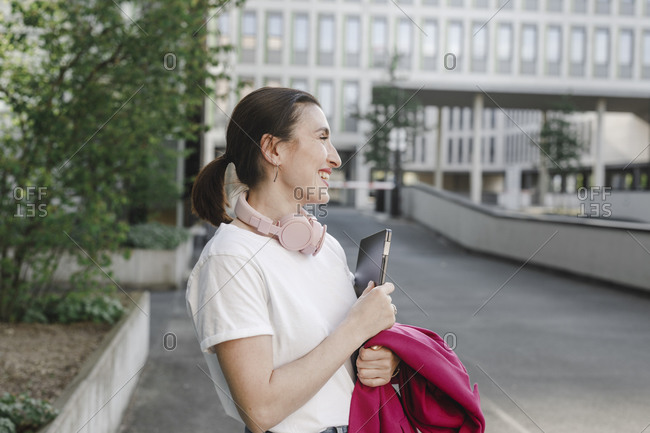 Happy businesswoman holding laptop while standing on street against office building