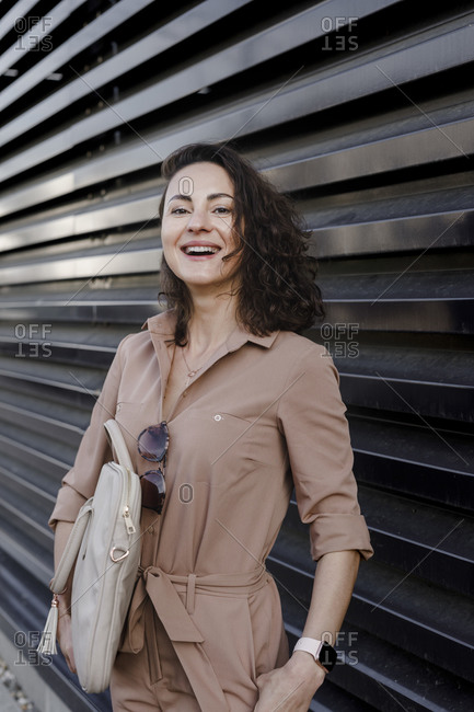 Portrait of contented businesswoman carrying laptop bag while standing against black shutter