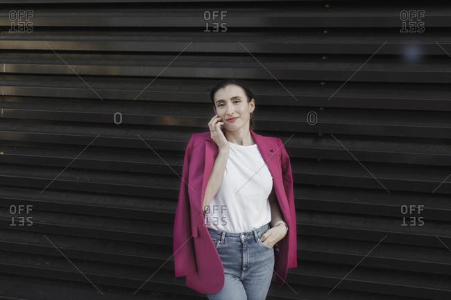 Portrait of confident businesswoman using smart phone against black shutter
