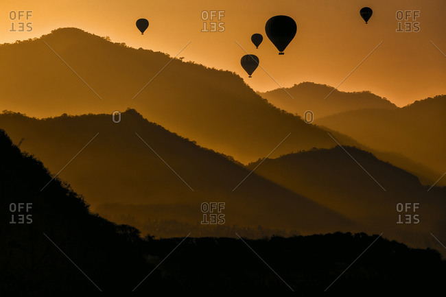 Indonesia- West Nusa Tenggara- Silhouettes of hot air balloons flying over Sumbawa island at moody dusk