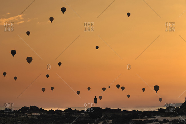 Indonesia- West Nusa Tenggara- Silhouettes of hot air balloons flying over lone woman standing on rocky shore at moody dusk