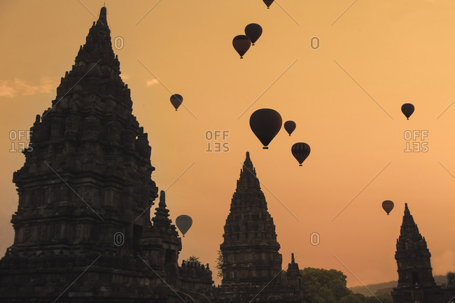 Indonesia- Java Island- Silhouettes of hot air balloons flying over Prambanan temple at moody dusk