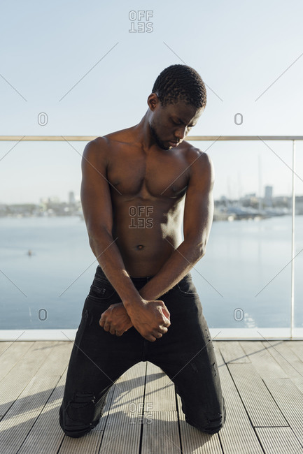 Black man kneeling with crossed hands on planks