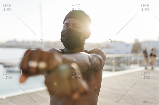 Black man with beanie and face mask- crossing fists