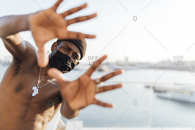 Black man with beanie and face mask- looking through his hands