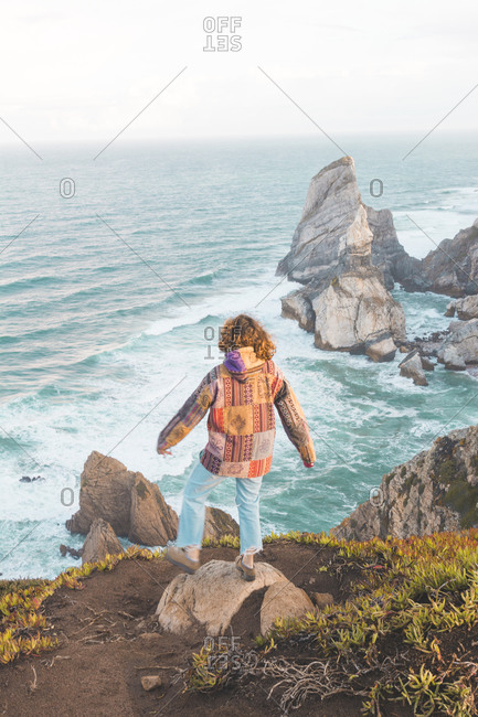 Full length rear view of young woman standing on rock at Ursa Beach- Lisboa Region- Portugal