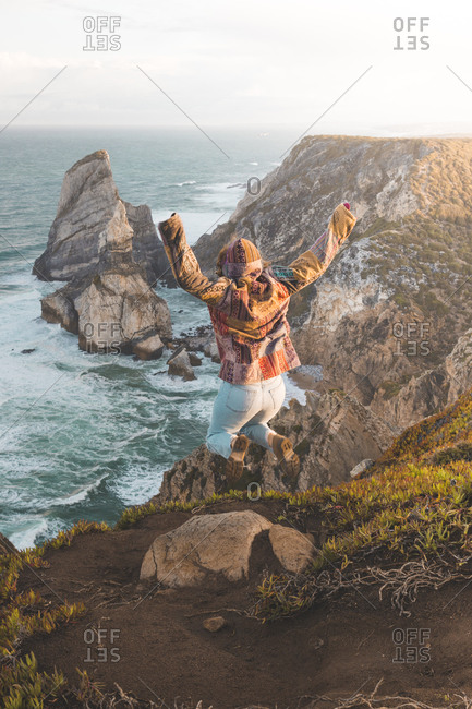 Full length rear view of young woman jumping on hill at Ursa Beach- Lisboa Region- Portugal
