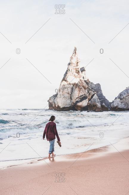 Full length rear view of woman walking on shore at Ursa Beach- Lisboa Region- Portugal