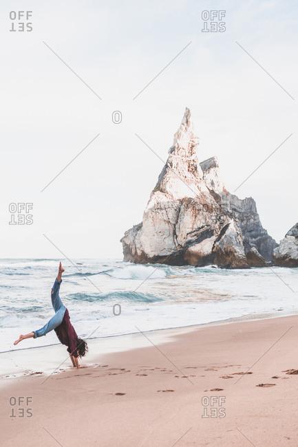 Full length of woman performing handstand on shore at Ursa Beach- Lisboa Region- Portugal