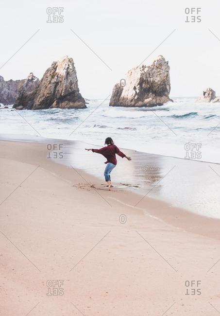 Full length of playful woman on shore at Ursa Beach- Lisboa Region- Portugal