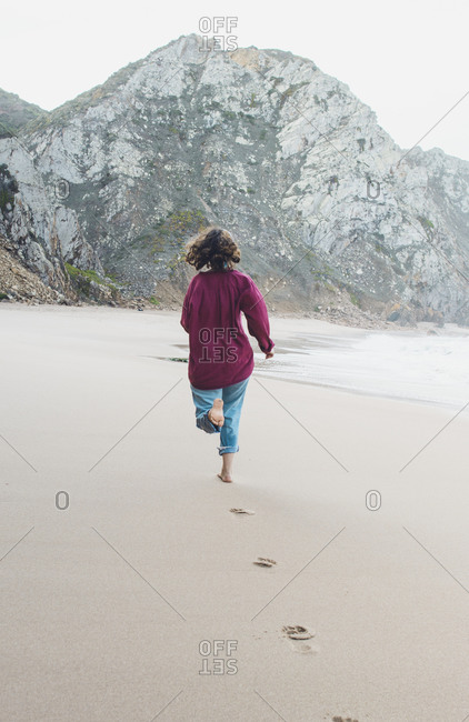 Young woman leaving footprints while running at Ursa Beach- Lisboa Region- Portugal