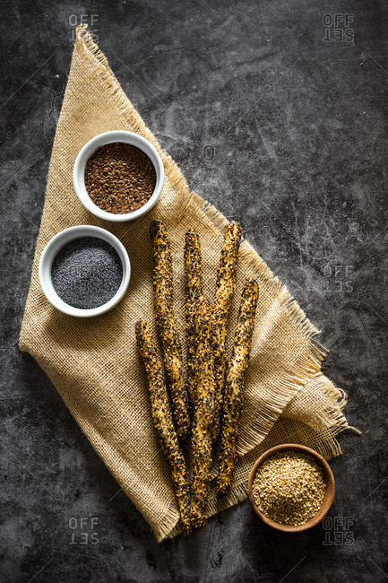 Place mat and fresh Italiangrissinibreadstickswith sesame- flax and poppy seeds