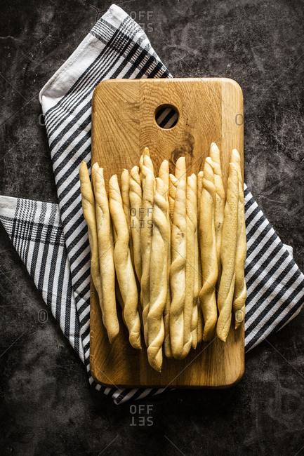 Cutting board with fresh Italian grissini breadsticks