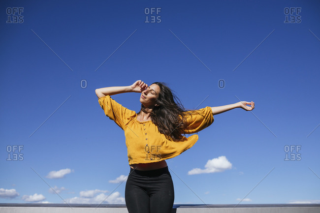 Carefree woman dancing on roof terrace in sunlight