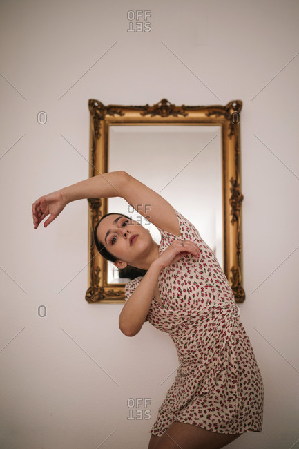 Portrait of ballerina performing dance against classic mirror on wall at home