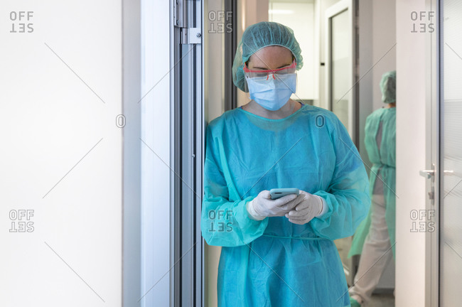 Female dentist text messaging through mobile phone while standing on doorway in medical clinic