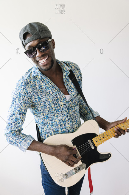 Portrait of smiling young male pop musician playing guitar against white background
