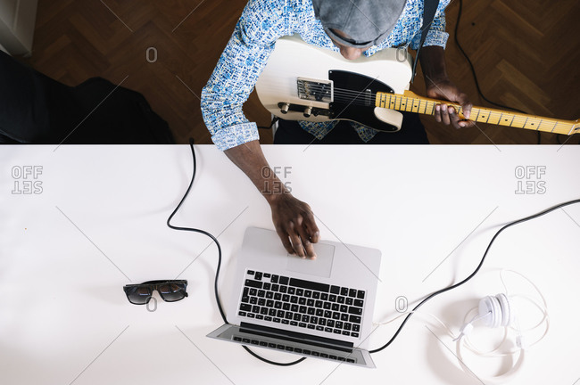 Young man learning to play guitar from internet at home