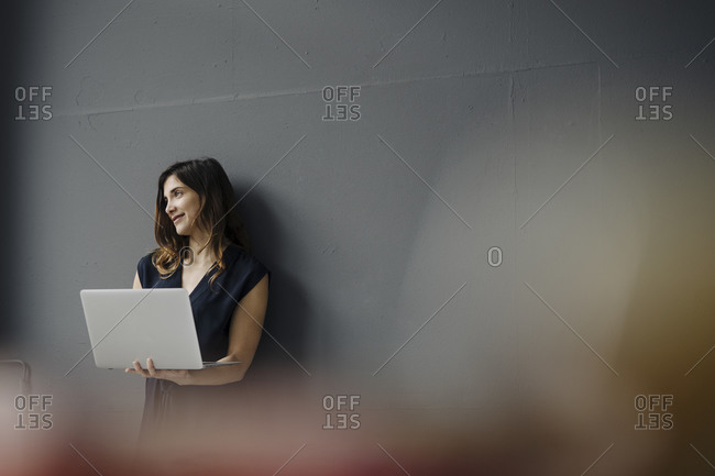 Portrait of smiling young woman with laptop leaning against wall looking at distance