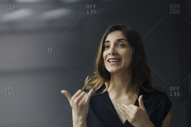 Portrait of gesturing young businesswoman against grey background