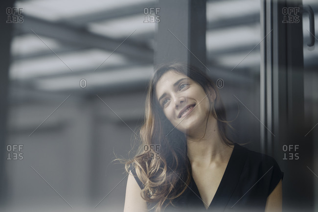 Portrait of smiling young businesswoman behind windowpane