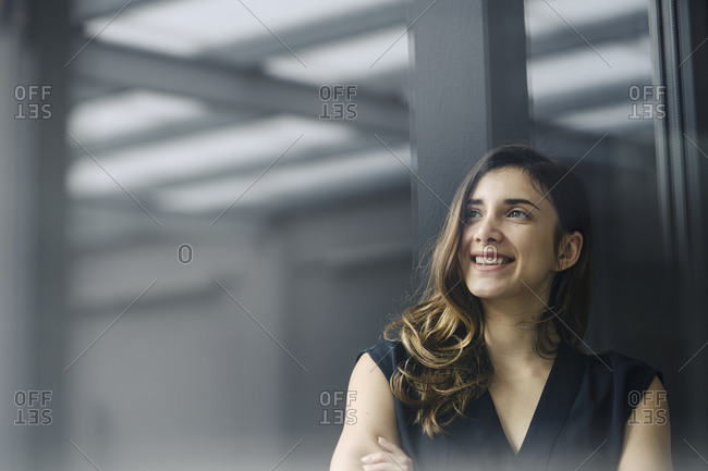 Portrait of smiling young businesswoman behind windowpane looking at distance