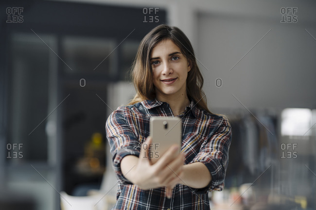Portrait of smiling young woman taking selfie in a loft
