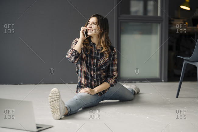Smiling freelancer on the phone doing the splits on floor of a loft looking at distance