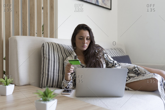 Beautiful young woman holding credit card for online shopping through laptop while lying on sofa at home