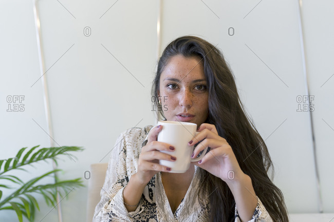 Portrait of young woman with freckles drinking coffee at home