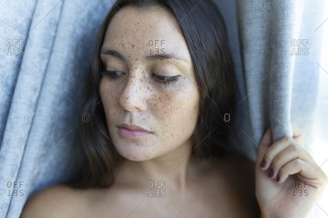 Close-up of beautiful young woman with freckles against curtain at home