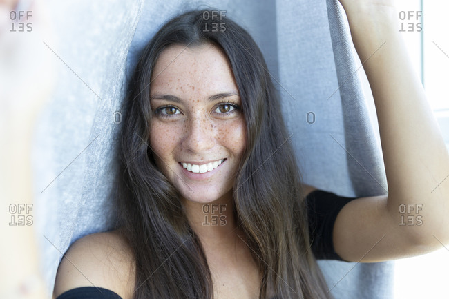 Close-up portrait of smiling young woman with freckles against curtain at home