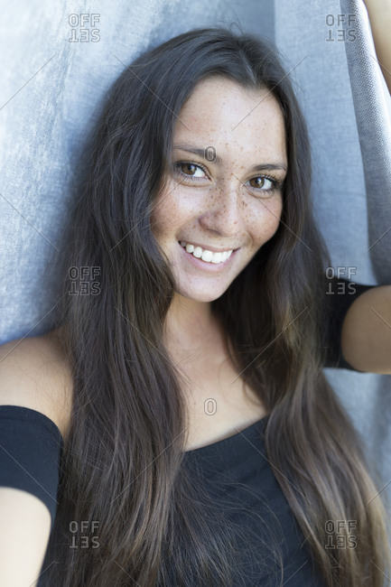 Close-up portrait of smiling young freckled woman against curtain at home
