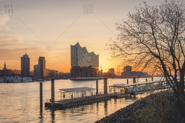 March 24,  2020: Germany- Hamburg- Empty harbor on bank of Elbe river at sunrise with Elbphilharmonie in background