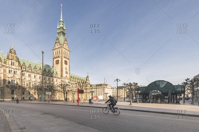 April 16,  2020: Germany- Hamburg- Cyclist passingHamburg City Hall