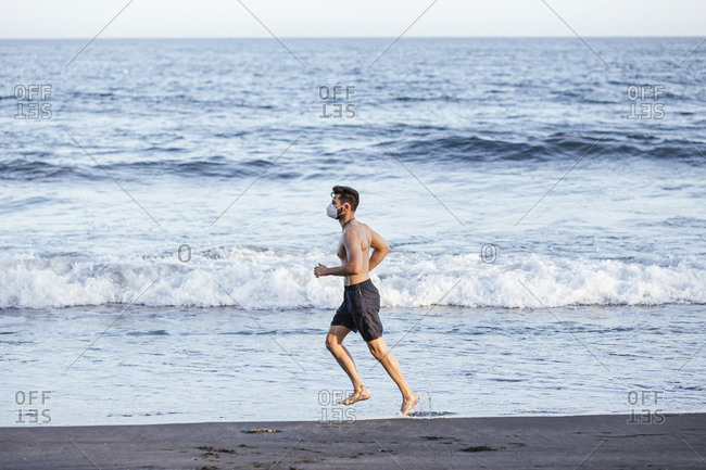 Side view of shirtless mid adult man wearing face mask while running at beach during sunset