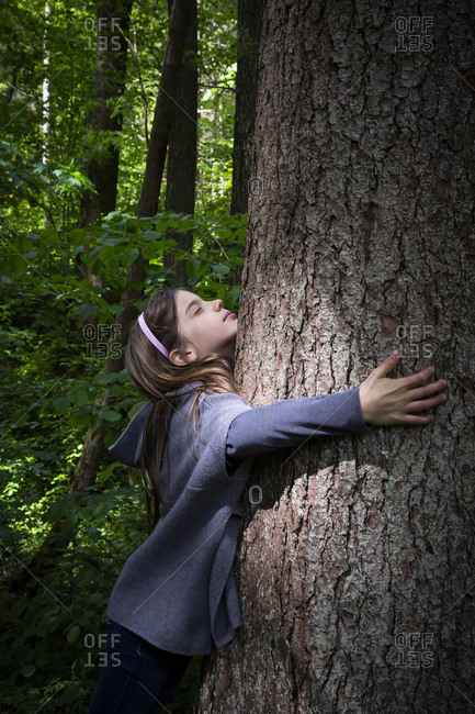 Cute elementary girl hugging tree trunk in forest