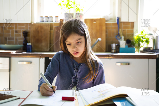 Girl doing homework in kitchen at home