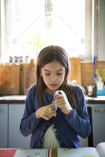 Girl cutting paper stripe during homework