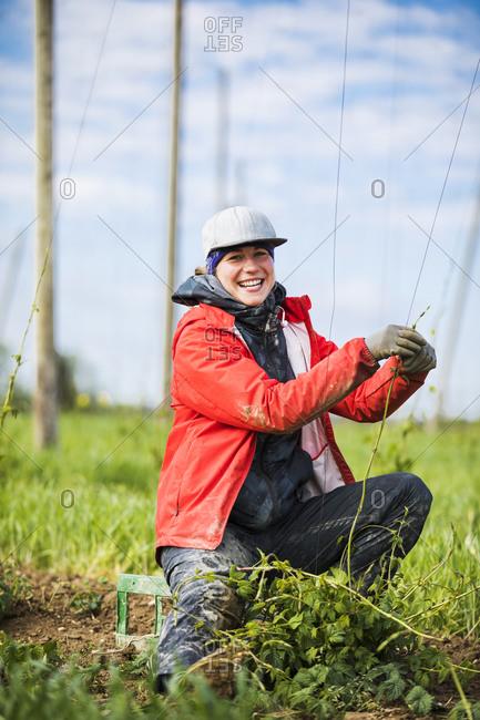 Portrait of happy female farmer planting hop crops on field at Hallertau- Bavaria- Germany