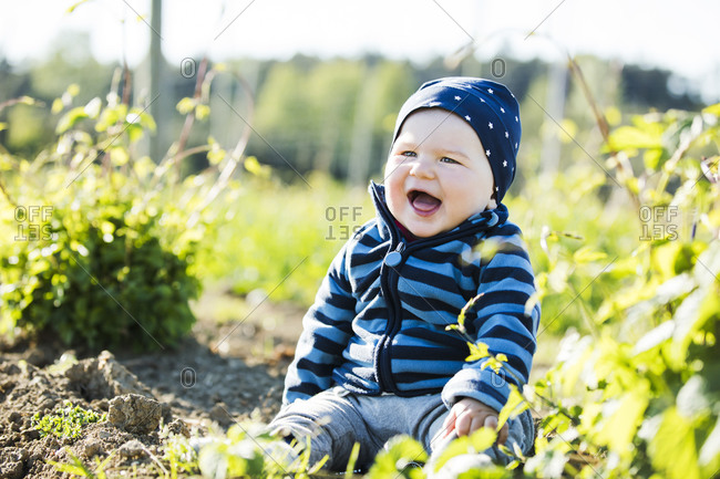 Cheerful baby boy sitting on hops field during sunny day
