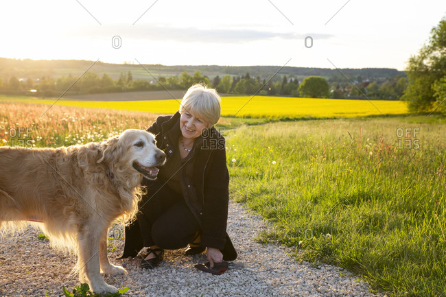 Germany- Bavaria- Neusass- Portrait of senior woman crouching in front of Golden Retriever in middle of countryside dirt road
